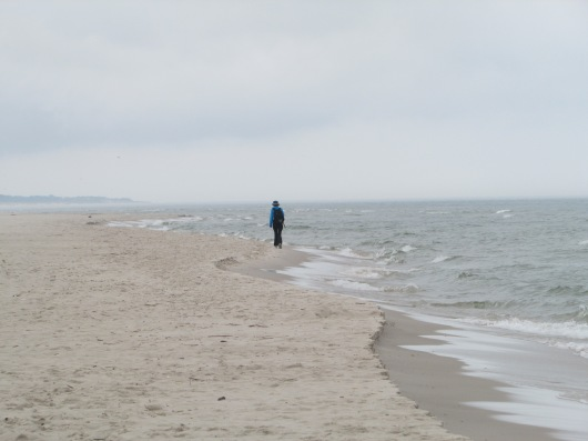 Woman walking alone on the beach at Leba, Poland